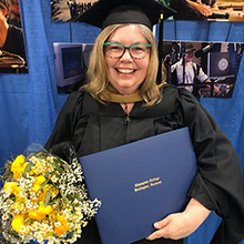 Lisa Barron smiles with her regalia and diploma in hand.