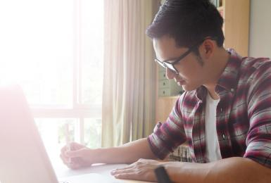 Young student on laptop at kitchen table