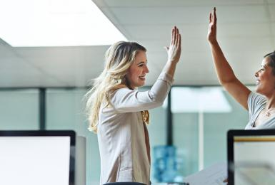 Two professionals giving each other high five in the workplace