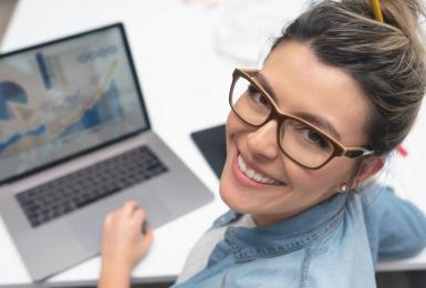 Female marketing professional working on laptop and smiling at the camera