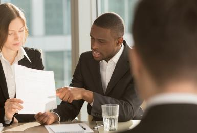 Professionals in an interview, reviewing a resume with online credentials