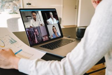 Manager holding video call with remote team on laptop