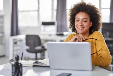 Female content strategist looking at laptop in office