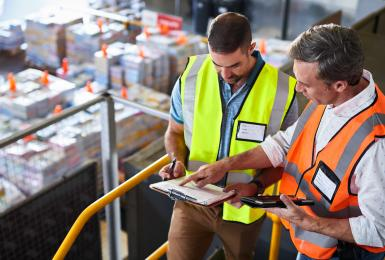 Two supply chain managers in warehouse looking at clipboard
