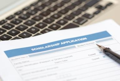 Printed scholarship application lying on laptop keyboard