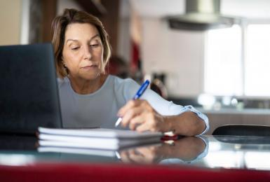 Mature woman taking notes next to a laptop computer