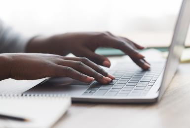 Photo of hands typing on a laptop