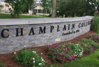 Stone sign that says Champlain College in front of campus building