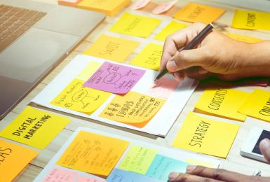 Image of person holding pen over multi-colored sticky notes on a desk