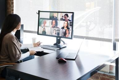 Business woman meeting with colleagues virtually on computer.
