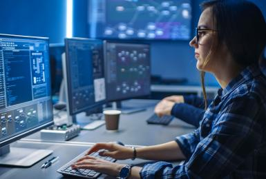 Female cybersecurity professional working on a computer.