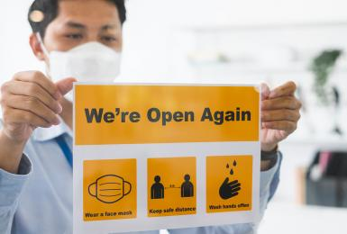 Asian businessman wear face mask attach reopen sign at office after lockdown due to coronavirus covid-19, business new normal and social distancing concept.