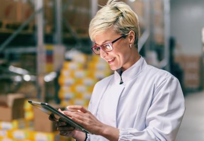 Female supply chain manager looking at tablet in warehouse