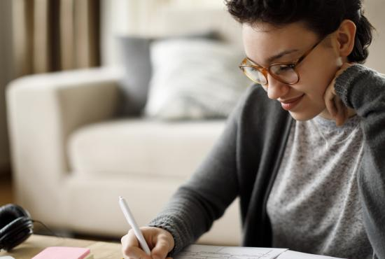 Smiling woman studying and filling out paperwork