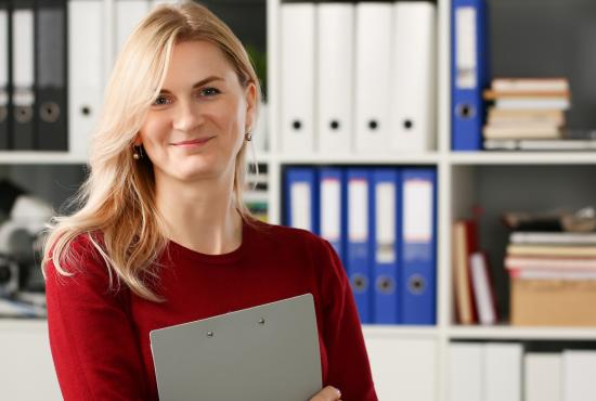 Female health care administration professional smiling in front of bookshelf
