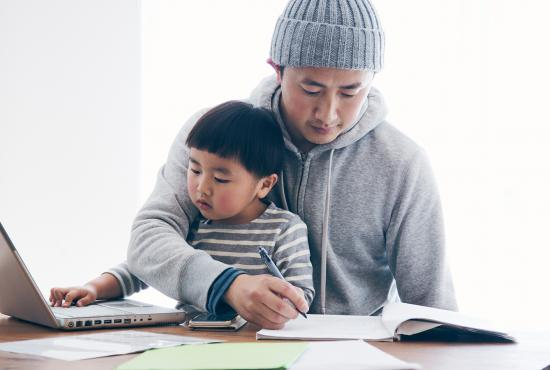 Japanese man in casual clothes writing a document and his son using a laptop on the desk. He's working and doing childcare at home.