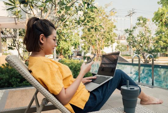 Young asian businesswoman using smart phone and typing on laptop computer for sharing social media sitting in bed at outdoor.