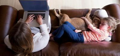 Adult student doing school work on laptop next to child and family dog