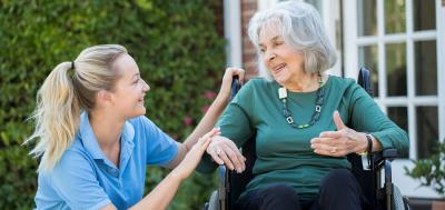 Elderly woman in wheelchair at home with home health worker