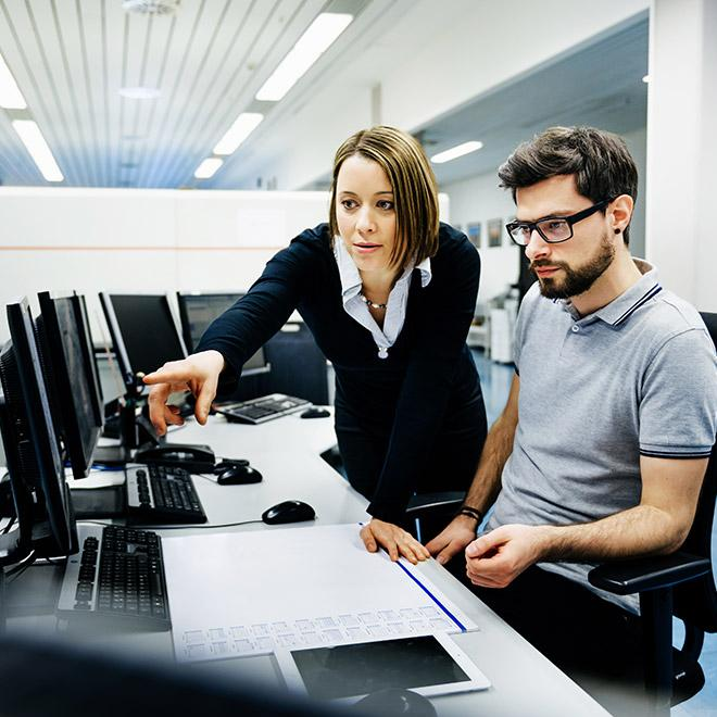 Cyber security professionals collaborating in computer lab