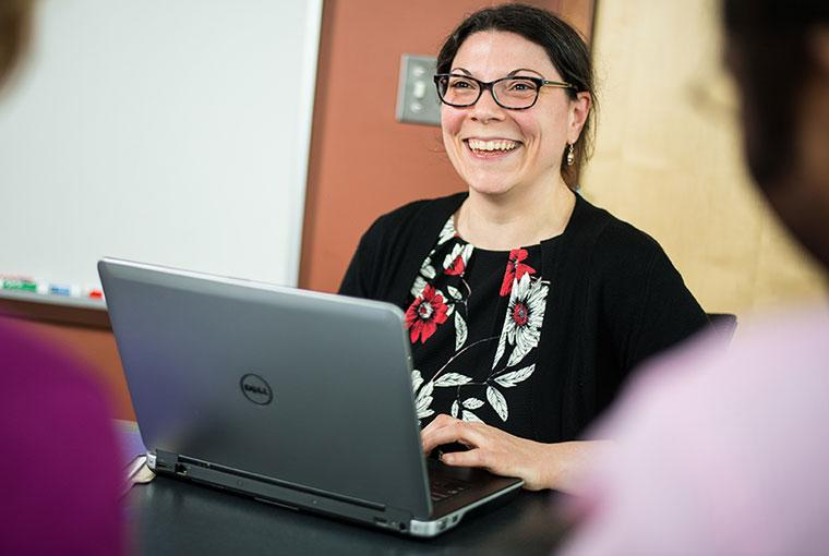 Champlain College Online advisor smiling with computer